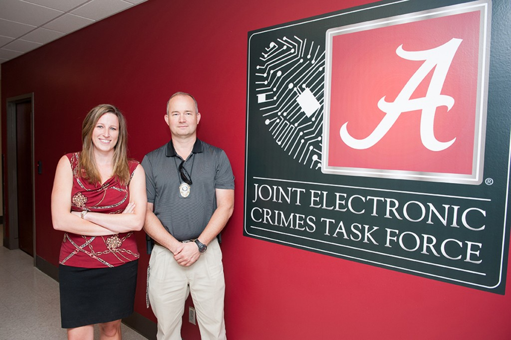 """a woman and a man standing next to a sign that reads """"Joint Electronic Crimes Task Force"""""""