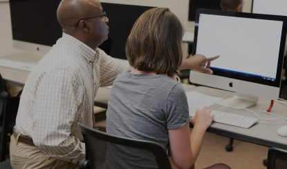 instructor assisting a student on an iMac